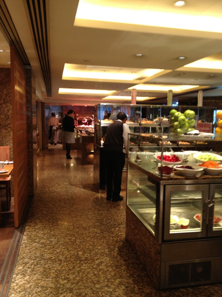 There are several rows of different items. The first row includes some fruits, the second breads, the third and fourth are various hot foods. There are also hot foods and cereals along the left side of the room.